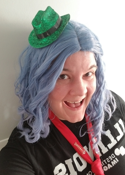 Kate Nylander poses in a tiny green hat for DI's Hats On For Creativity fundraising challenge